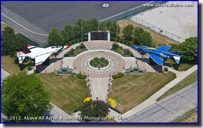 A low and close helicopter aerial view of the Marjorie Rosenbaum Plaza at Burke Lakefront Airport in downtown Cleveland, Ohio.
