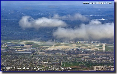 A distant oblique aerial view of Cleveland Hopkins International Airport under some fair weather cumulus clouds as viewed from above Independence, OH