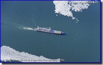 A freighter on Lake Erie passes between some clumps of ice