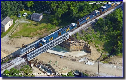 An aerial view of a freight train crossing a temporary steel bridge near Columbus, OH