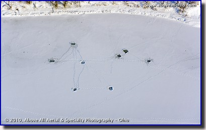Aerial view of ice fishing holes drilled into a frozen lake near Pittsburgh, Pennsylvania