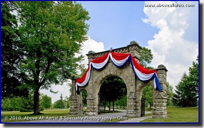 An architectural photograph of the entrance to a cemetery decorated for Memorial Day; Medina, Ohio