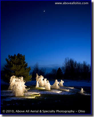 A crescent moon shines above a Christmas display of life sized angels at dusk at a home near Willard, Ohio
