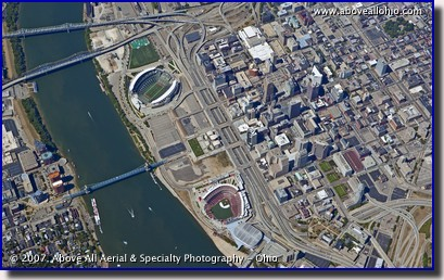 A very steep oblique aerial view of downtown Cincinnati, OH, showing the Ohio River, Paul Brown Stadium, and Great American Ballpark.