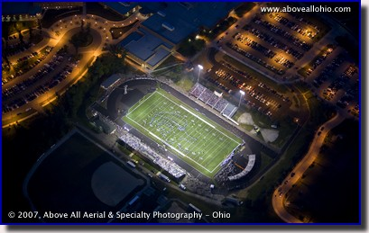 Night time aerial photo of a Friday night high school football game under the lights