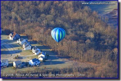 A colorful hot air ballon floats over Ohio in very early spring