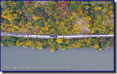 A vertical aerial image of a freight train between a river and fall colored trees in PA