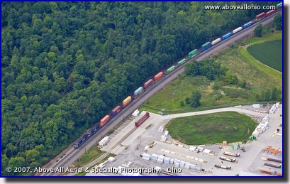 Aerial view of a lumber yard and a very wooded area separated by train tracks in Pennsylvania