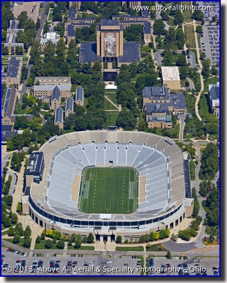 "An aerial photo of the University of Notre Dame Stadium and the ""Touchdown Jesus"" mural in South Bend, Indiana."