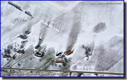 An aerial view of snowy fields showing how the wind is affected by buildings and trees.